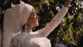 En härlig ung flicka ser den ljusa solen till och med hennes fingrar Henne grimaser glatt i solen Mycket trevligt skott arkivfilmer