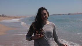 En härlig ung flicka som har gyckel på stranden långsam rörelse arkivfilmer