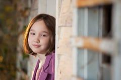 En härlig ung flicka som kikar ut från ett hus Royaltyfria Bilder