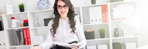 En härlig ung flicka står nära ett kontorsskrivbord och rymmer en penna och en anteckningsbok i henne händer Flickan förhandlar royaltyfria foton
