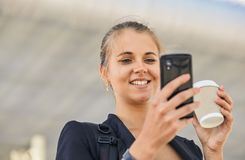 En härlig ung kvinna använder en app i hennes smartphoneapparat för att överföra ett textmeddelande royaltyfri foto