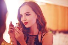 En härlig ung kvinna gör sig en makeover Flicka med cerly hår som gör aftonmakeup genom att använda läppstift framme av spegel I arkivfoto