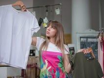 En härlig ung kvinna i en shoppa som väljer mellan två T-tröja på ett ljus - grå suddig bakgrund Royaltyfri Bild