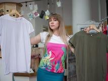 En härlig ung kvinna i en shoppa som väljer mellan två T-tröja på ett ljus - grå suddig bakgrund Fotografering för Bildbyråer