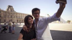 En härlig ung kvinna med mörkt hår i en svart t-skjorta och en ung gladlynt grabb i en skjorta att ta en selfie l?ngsam r?relse arkivfilmer