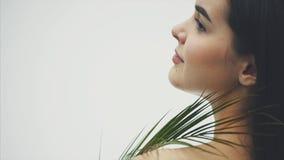 En härlig ung kvinna med perfekt hud och naturlig makeup poserar framme av kameran Tropiska gröna sidor av lager videofilmer