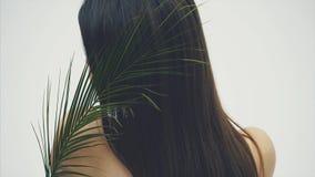 En härlig ung kvinna med perfekt hud och naturlig makeup poserar framme av kameran Tropiska gröna sidor av arkivfilmer