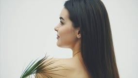 En härlig ung kvinna med perfekt hud och naturlig makeup poserar framme av kameran Tropiska gröna sidor av stock video