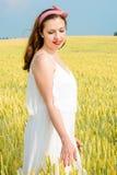 En härlig ung kvinna på ett vetefält arkivfoto