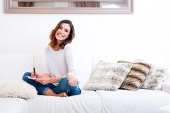En härlig ung kvinna på soffan Arkivbild