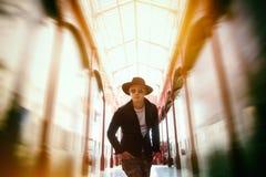 En härlig ung man i svart skjorta och svart hatt royaltyfria bilder