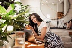 En härlig ung slank flicka med mörkt hår och exponeringsglas, iklädd tillfällig stil, sitter på tabellen med en bärbar dator i et fotografering för bildbyråer