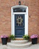 En härlig välkomnande blå ytterdörr med en välkommen krans Royaltyfri Bild