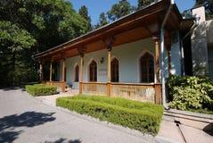 En härlig veranda med ett trätak och pelare mot bakgrunden av gräsplanen parkerar zon arkivfoto