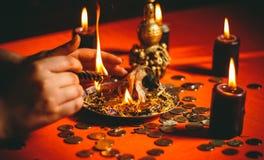 En häxa rymmer en ritual för pengar royaltyfria foton