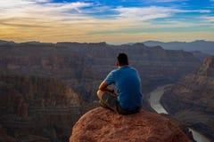 En hållande ögonen på solnedgång för man på Grand Canyon arkivbilder