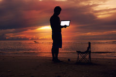 En hållande bärbar dator för man med den vita skärmen på stranden Royaltyfri Bild