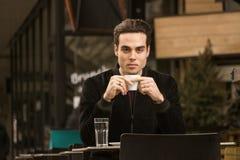 En hållande kaffekopp för ung allvarlig man Royaltyfri Bild