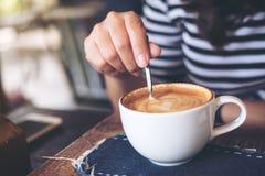 En hållande kaffesked för kvinna och ett varmt kaffe för stirring Royaltyfri Fotografi