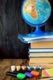En hög av böcker, jordklotet, målarfärger och highlighters Arkivbilder