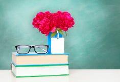 En hög av böcker och blommor i en vas på en trätabell Royaltyfri Foto