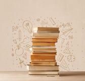 En hög av böcker på tabellen med dragit klotter för skola handen skissar Royaltyfri Foto