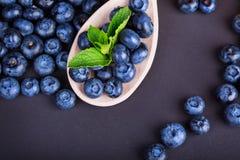 En hög av blåbär med den gröna mintkaramellen i en träsked på en purpurfärgad bakgrund Healthful ingredienser för sommarfruktsall royaltyfria foton
