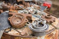 En hög av gamla brutna stycken av järn som ligger på en rostig trumma Arkivbild