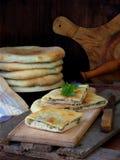 En hög av georgiska pajer med ost och våren gör grön på en träbakgrund Utrymme för text royaltyfri bild