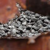 En hög av kol bak en rostig metallvägg royaltyfria foton