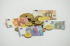 En hög av mynt, det europeiska valutaEUROET med miniatyrsedlar 5, 10, 20, EURO 50 Isolerat på vit bakgrund med clippin Arkivfoto