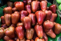 En hög av ny rosa äpplefrukt på bananbladet som är till salu på marknaden arkivbild