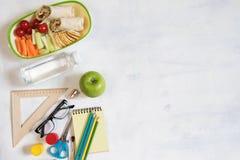 En hög av olik brevpapper på tabellen, notepad, färgade blyertspennor, linjal, markör, hyvlare, utrymme för text Läcker skolalunc royaltyfri foto