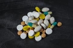 En hög av preventivpillerar och kapslar på en tabell Arkivbilder