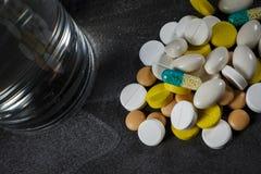 En hög av preventivpillerar och kapslar på en tabell Arkivfoton