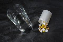 En hög av preventivpillerar på en tabell med ett exponeringsglas av vatten Royaltyfri Foto