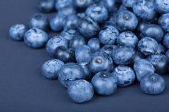 En hög av söta och naturliga blåbär på ett mörker - blå bakgrund Organiska ingredienser för sunda mellanmål royaltyfri fotografi