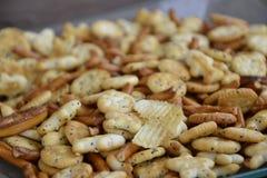 En hög av smällare, potatischiper och pinnar i en bunke Arkivfoton