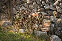 En hög av tegelpannor som framme ligger av en stenvägg arkivfoton