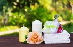 En hög av vita mjuka handdukar, doftande olja, rosor och stearinljus på en suddig grön bakgrund Tvål-, handduk- och blommasnowdro Arkivbild