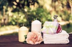 En hög av vita mjuka handdukar, doftande olja, rosor och stearinljus på en suddig grön bakgrund Tvål-, handduk- och blommasnowdro Royaltyfria Bilder