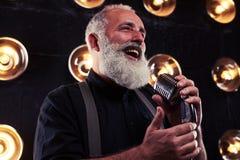 En hög Caucasian skäggig man med sjungande jazz för mikrofon royaltyfri foto