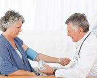En hög doktor som tar blodtryck Arkivfoton