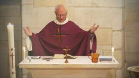En hög fransk katolsk präst ger mass under ett dop i Aquitaine arkivbild