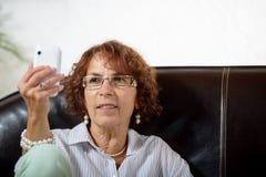 En hög kvinna med en telefon Fotografering för Bildbyråer