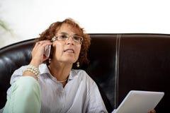 En hög kvinna med en telefon Royaltyfria Bilder