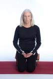 En hög kvinna mediterar Arkivfoto