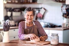 En hög kvinna som hemma knådar deg i köket royaltyfri foto