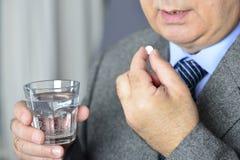 En hög man som tar medicin med ett exponeringsglas av vatten Arkivfoton