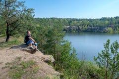 En hög vit man med ryggsäcksammanträde på vagga nära sjön och håller en framsida till solen royaltyfria bilder